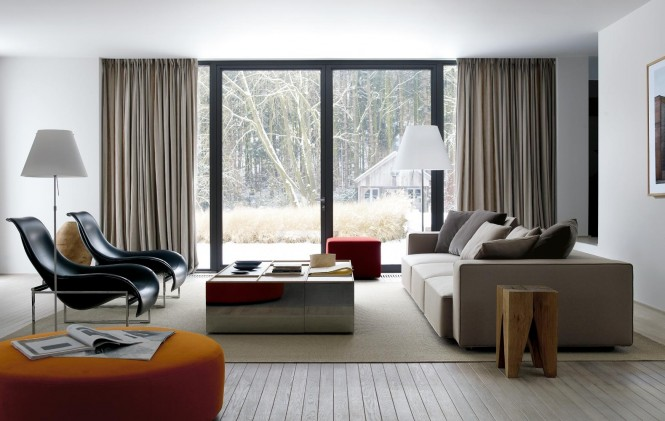 charming-living-room-with-sofa-cushions-red-pouffe-and-large-orange-pouffe-contemporary-black-chairs-wooden-floor-covered-by-brown-carpet-bay-window-with-beige-curtain-and-lamps
