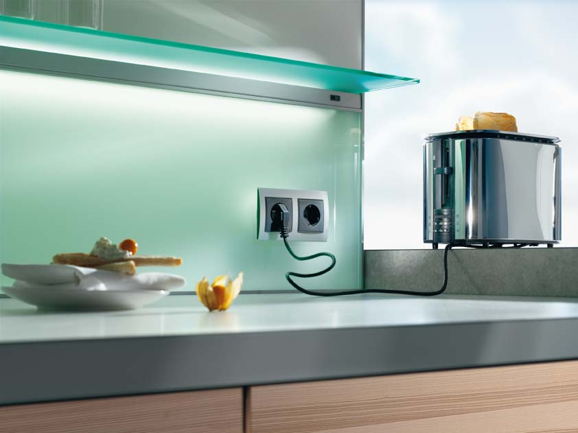 kitchen-rear-wall-has-a-backlit-glass-niche-with-integrated-socket
